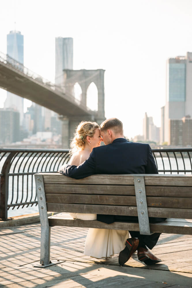 Bride and groom sitting on bench with Brooklyn Bridge. Braut und Bräutigam, die auf Bank mit Brooklyn-Brücke sitzen.